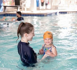 Female Instructor Holding Female Child Swimmer