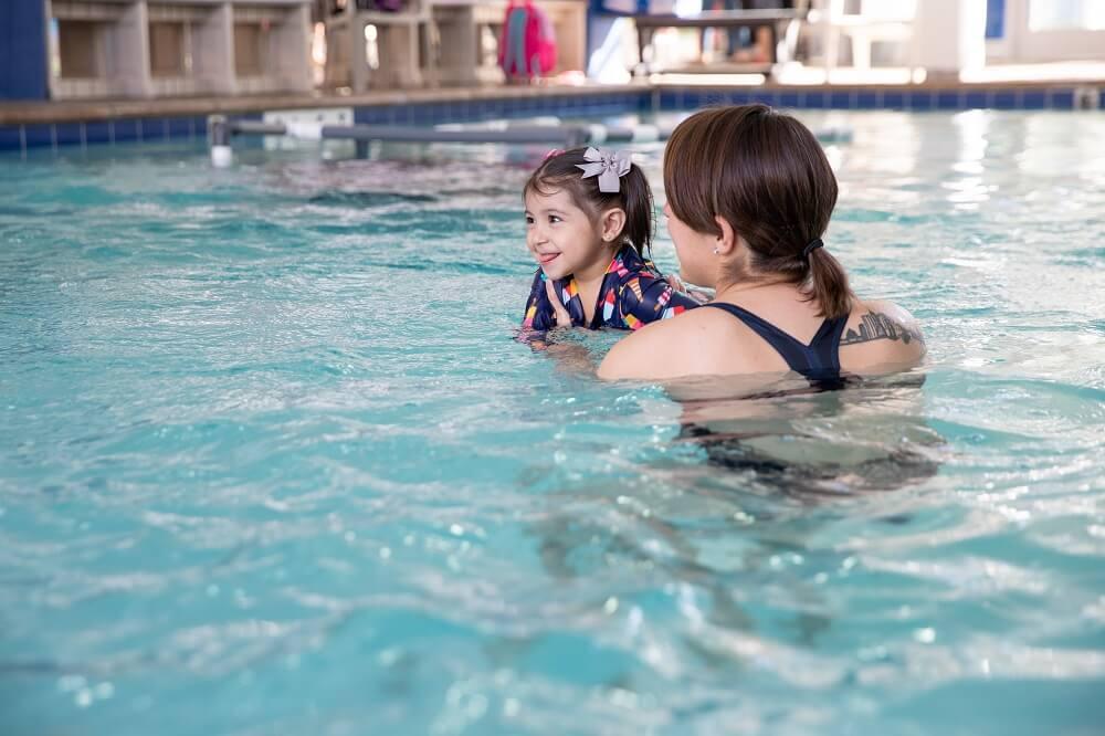 Female Instructor Teaching Female Child How to Swim