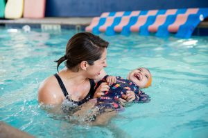 Female Instructor Holding Female Child in Pool